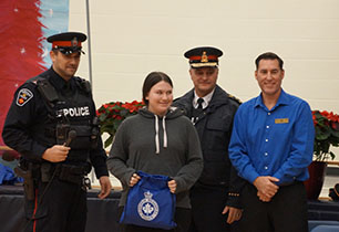 Female student standing with two male police officers and male manager from LCBO