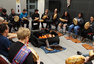 Male and female students introducing themselves to the Metis drums