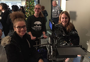 Three female students behind a film industry camera learning about the trade.
