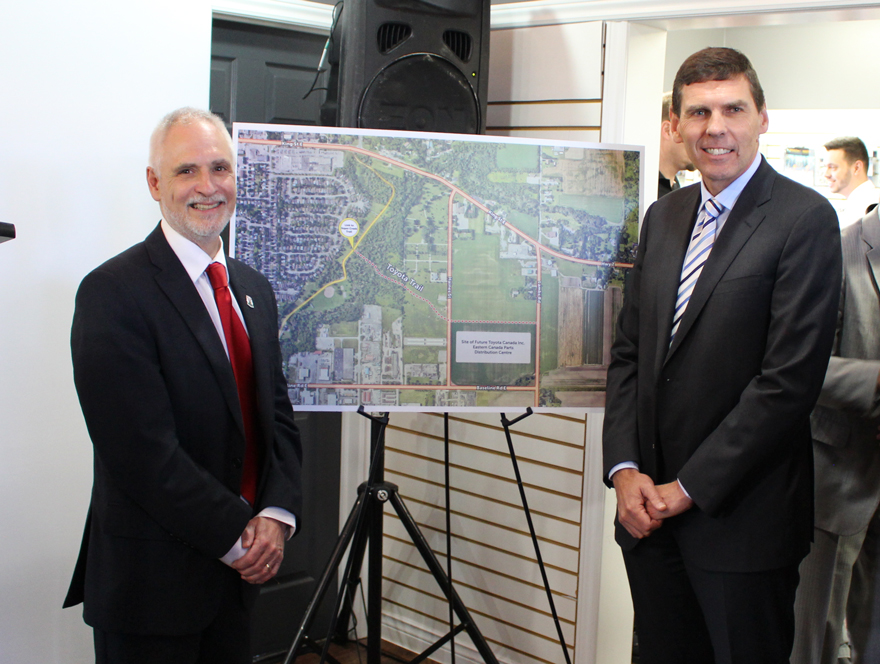 Clarington Mayor Adrian Foster with Larry Hutchinson, President and CEO of Toyota Canada Inc. in front of the proposed Toyota Trail display