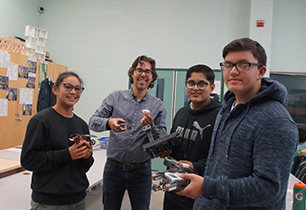 Male student standing with female student and two male students holding items created in technology class