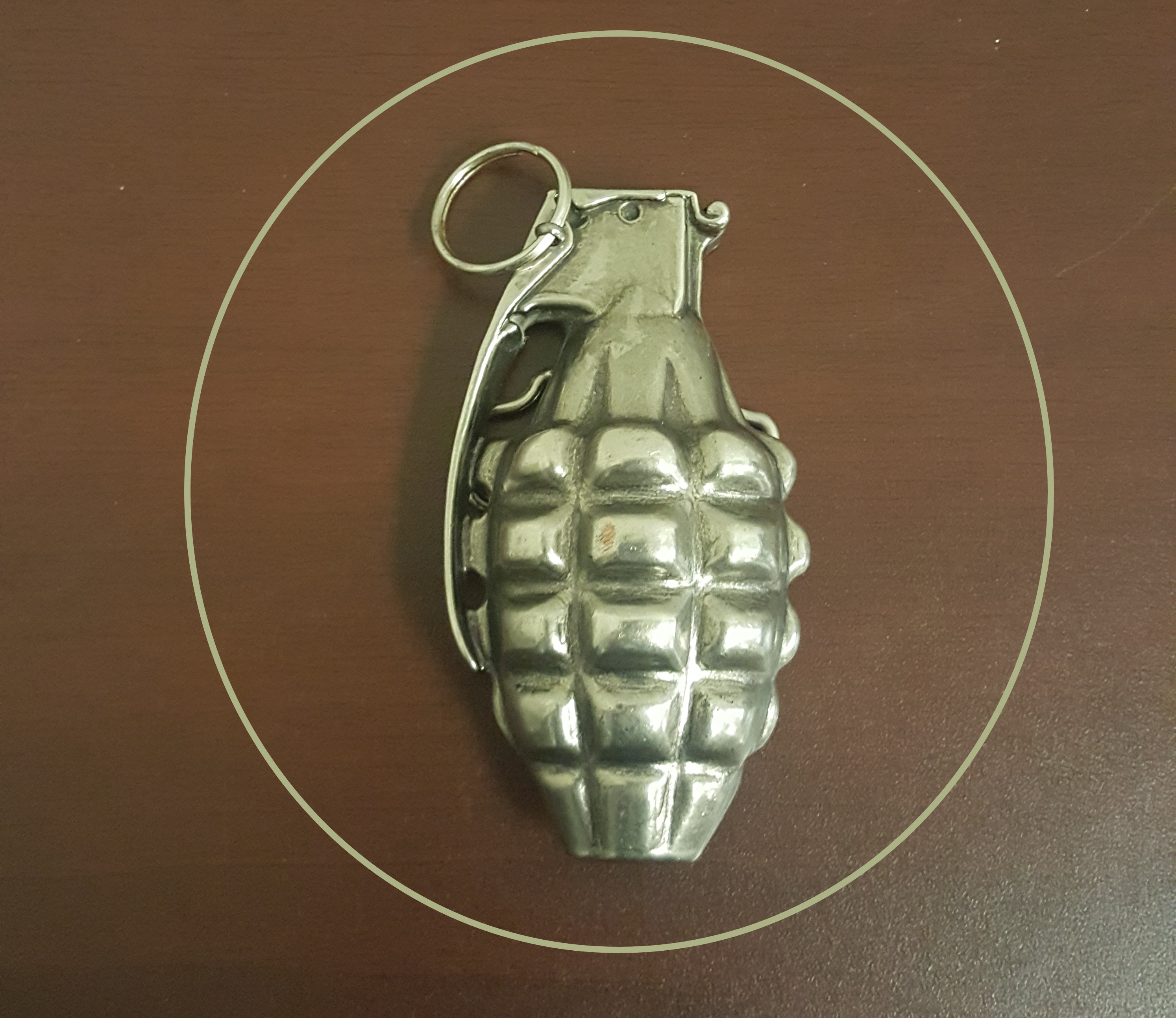 This is an image of a belt buckle in the shape of a hand grenade