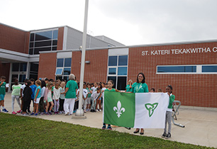 Two female students holding Franco-Ontario flag with female adult principal