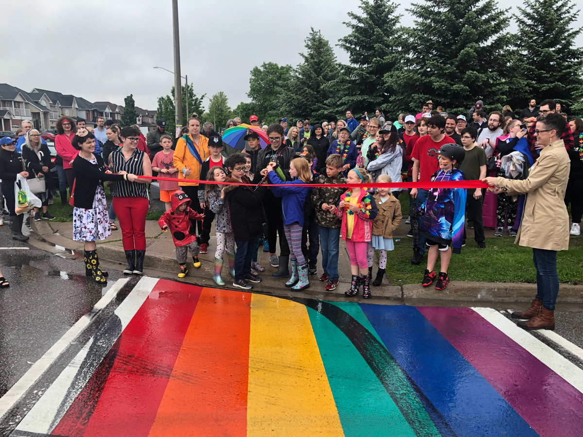 Children cut a ribbon at the Rainbow Crosswalk Dedication Ceremony
