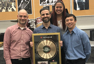 Three male adults and a female adult holding a gold record award