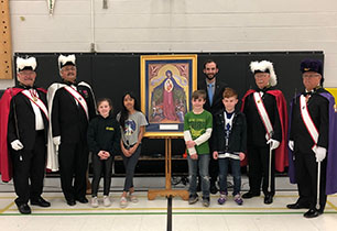 Five male adults standing with photo of Blessed Mother Mary and three students