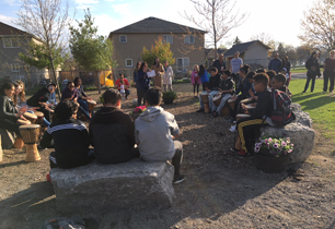 students and adults standing and sitting in the Outdoor Classroom area