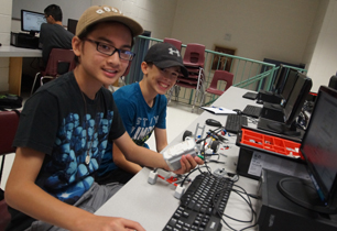 Two male students building and coding their robot