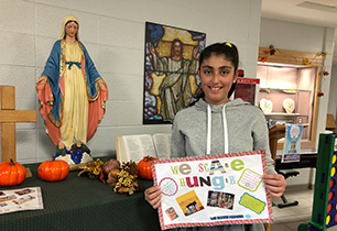 Female student holding poster that says We Scare Hunger
