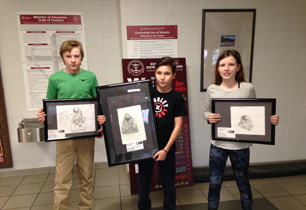 Three students holding their pencil drawings
