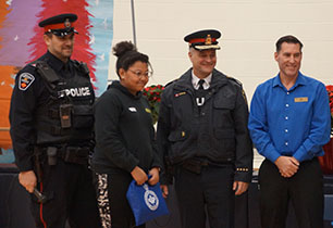 Female student standing with two male police officers and LCBO manager