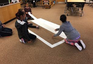 Students doing math on a carpet