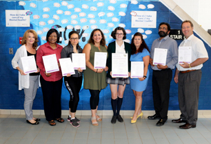 Female student standing with female and male staff holding the Premier Award for Safe Schools