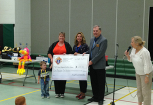 Adults presenting a cheque to the school