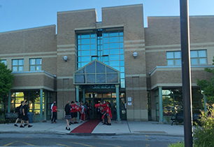 Exterior of school with students and staff welcoming students on a red carpet