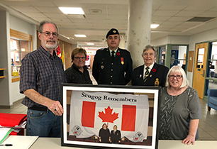 Male and female adults holding a pictures of female adults standing with Canadian flag