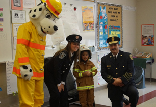 Female student wearing a fire fighters costume standing with the Fire Chief and Sparkie the Fire Dog