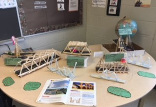 bridges made out of Popsicle sticks displayed on a table