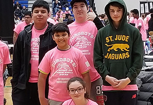 Group of male and female students wearing pink tshirt at Robots competition