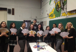 Female students holding letters with male adult