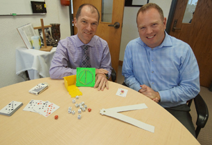 Two male adults with math items on a table