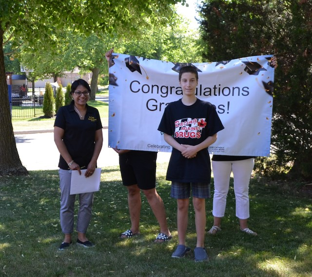 Six members of the school staff wearing masks and holding a banner congratulating Grade 8 grads
