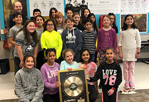 A group of students with their male teacher holding a gold record award