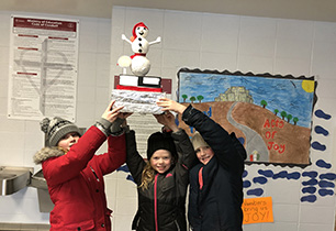 Three female students holding up a snowman