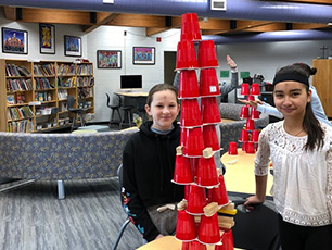Two female student standing behind their tower built with plastic cups