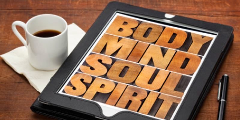 Cup of coffee with board saying Body, Mind, Soul and Spirit