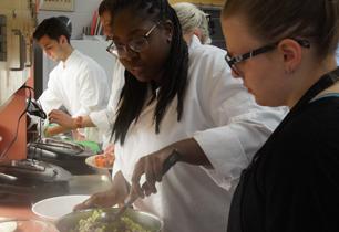 Female student mixes ingredients into the potato salad