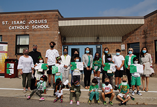 Group of male and female students and staff wearing green and white outside