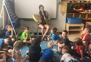 Female adult playing a hand drum and singing to Kindergarten students