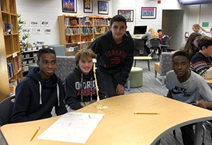 Four male students build a tower out of spagetti noodles