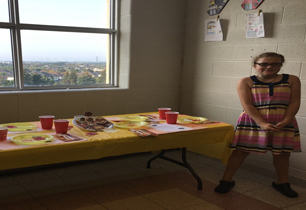 female student standing beside a table with food