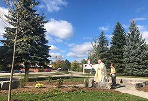 Priest blessing an outdoor garden