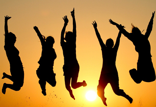 Students jumping in the air with sun rising in the background