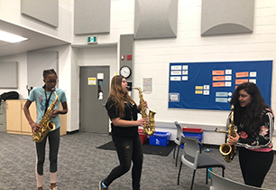 Three female students playing saxophones