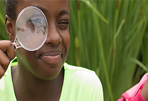 Female student holding a magnify glass up to her eye