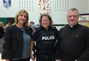Two female adults standing with a Priest