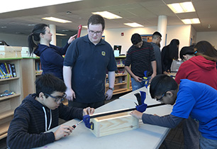 Male secondary students supports two male students as they build a wooden box