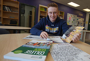 Male student looking at post secondary books
