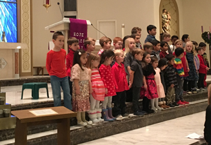 Students singing in front of the alter of a church