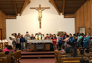 Priest standing on alter with students and staff around him
