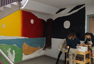 Three female students gather paint supplies beside Indigenous mural