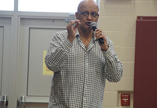 Male adult talking and holding a microphone