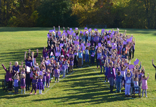 students and staff dressed in purple form a ribbon outside