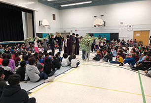 Students in a gym performing the living advent wreath