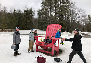 Group of male students hanging out on a giant red chair outside in the snow