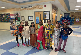 Eight female students dressed in traditional clothing representing their heritage